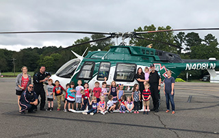 LifeNet Air medical helicopter flight crew pose with kids from Magnet Cove Elementary School during community helper's week.