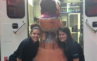 Lake Catherine Halloween in the Park, LifeNet EMS staff poses with a kid in a dinosaur costume.