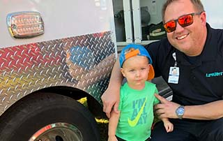 LifeNet Paramedic Justin Woodson stands with a little boy at National Night Out in Texarkana.
