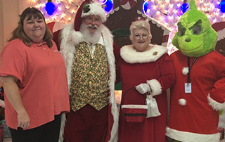 LifeNet EMS brings the Grinch to the TAPD Cops and Kids Dinner. LifeNet Biller Karen Clapp poses with Santa, Ms. Clause, & the Grinch.