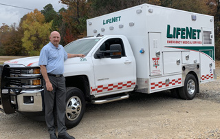 LifeNet General Manager Kelly McCaulley stands in front of a new ambulance.