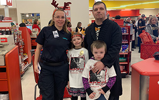 LifeNet Director of Marketing, Tina Bell, shops with a family at Target during the 2018 Shop with a Cop Event.