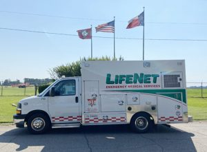 A LifeNet ambulance sits parked in front of the Arkansas, Texas, and American Flags at the Texarkana Regional Airport.