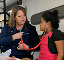 LifeNet EMT teaches a child how to hear a heartbeat using a stethescope during a Teddy Bear Clinic at LifeNet in Malvern.