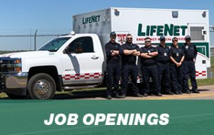 A group of LifeNet EMTs and paramedics stands in front of a LifeNet ambulance in Stillwater, Oklahoma.